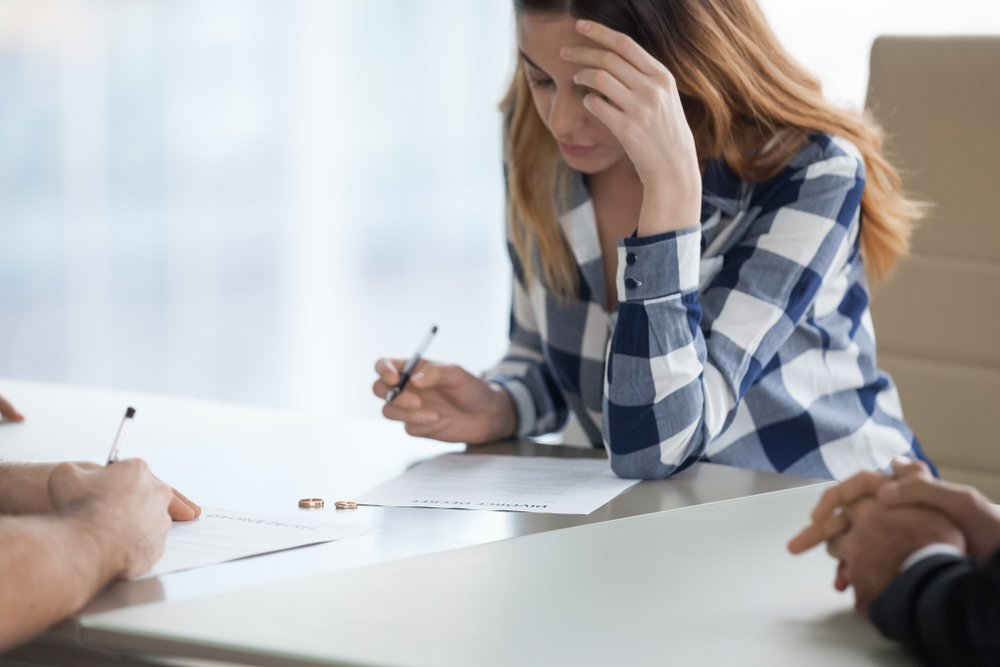 Woman signing an annulment paper.